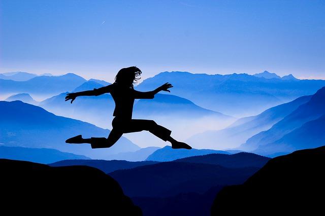 Personne qui saute d'une montagne à une autre